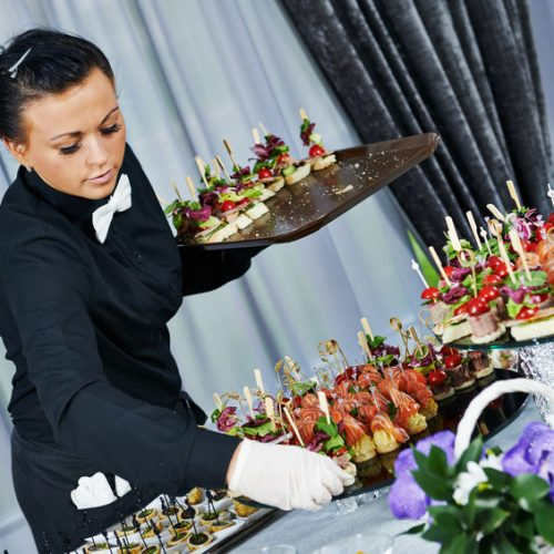 32615831 - waiter with meat dish serving catering table with food snacks during party event