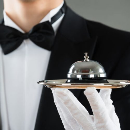 48645369 - midsection of waiter holding service bell in plate against gray background
